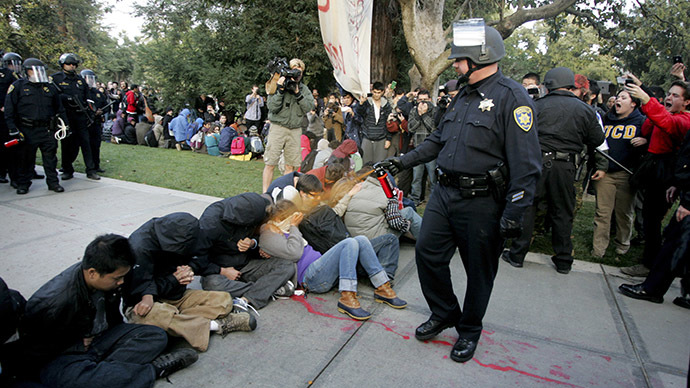 "A University of California Davis police officer pepper-sprays students during their sit-in at an ""Occupy UCD"" demonstration in Davis, California November 18, 201. (Reuters/Brian Nguyen)"