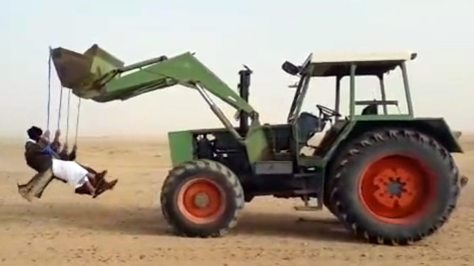 ​Having fun in Saudi desert: Daredevils swinging from reversing tractor (VIDEO)