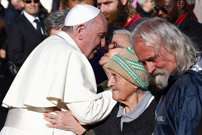 Pope Francis, who's 78th birthday is today, blesses a homeless person at the end of his general audience at the Vatican, December 17, 2014. (Reuters/Tony Gentile)