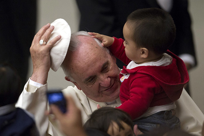 Pope Francis has his skull cap removed by a child during an audience with children assisted by volunteers of Santa Marta institute in Paul VI hall at the Vatican December 14, 2013. (Reuters/Giampiero Sposito)