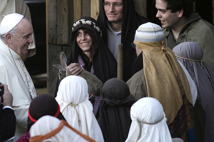 Pope Francis smiles with people dressed as characters from the nativity scene as he arrives to visit the Church of St Alfonso Maria dei Liguori in the outskirts of Rome January 6, 2014. (Reuters/Max Rossi)