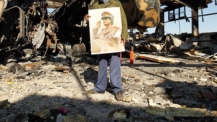 A Libyan holds a poster of Libya's leader Muammar Gaddafi (Reuters / Zohra Bensemra)