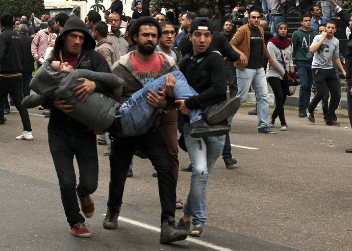 Anti-government protesters help an injured protester when pro-government protesters threw stones during a protest in front of the press syndicate in Cairo January 25, 2015. (Reuters/Asmaa Waguih)