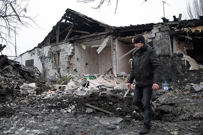 A man walks near a damaged residential building in Donetsk, eastern Ukraine January 19, 2015 (Reuters / Alexander Ermochenko)