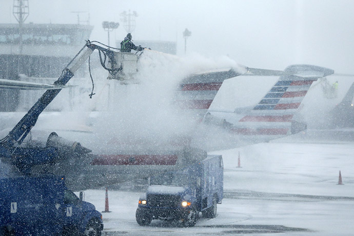 An airport worker de-ices an airplane at LaGuardia Airport New York January 26, 2015. (Reuters/Shannon Stapleton)