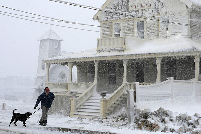 A man walks his dog past an ocean front house covered in ice during a winter blizzard in Marshfield, Massachusetts January 27, 2015. (Reuters/Brian Snyder)