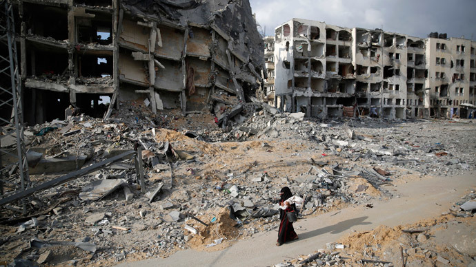 A Palestinian woman walks past buildings destroyed by what police said were Israeli air strikes and shelling in the town of Beit Lahiya in the northern Gaza Strip August 3, 2014.(Reuters / Finbarr O'Reilly)