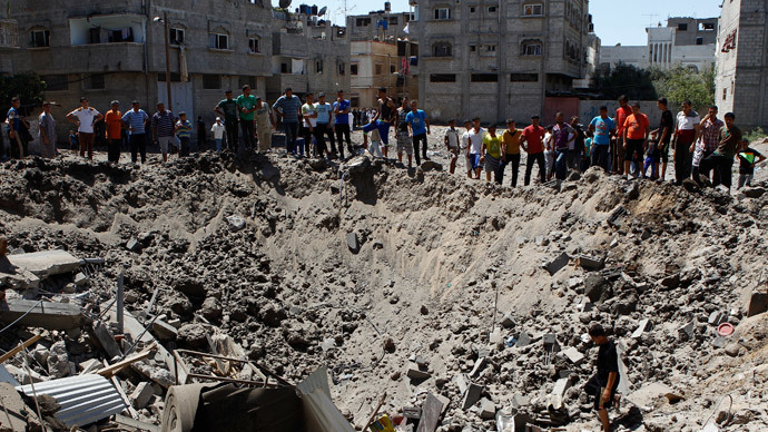 People look at a crater on the ground and damaged buildings, that witnesses said was caused by an Israeli air strike, in the Zeitoun neighbourhood in Gaza City August 8, 2014.(Reuters / Siegfried Modola)