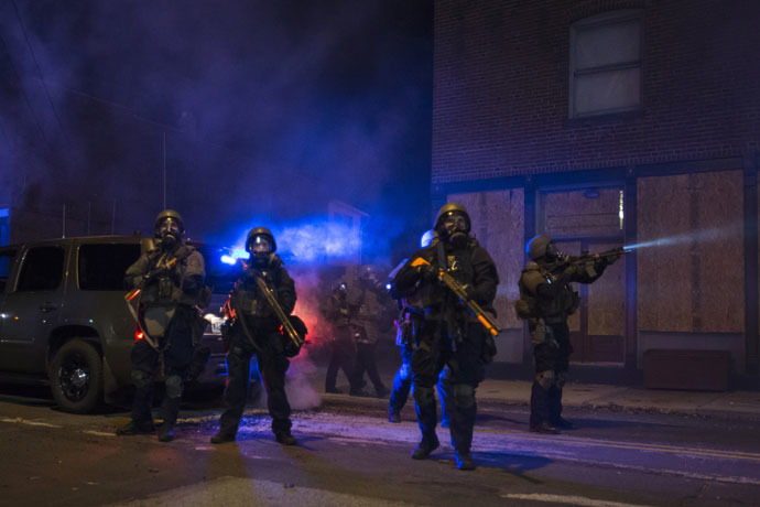Police in riot gear stand guard after deploying tear gas to disperse protesters in Ferguson, Missouri, November 25, 2014. (Reuters/Adrees Latif)