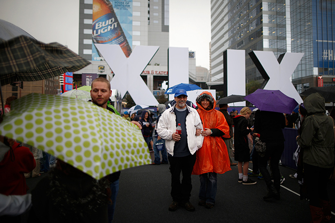 Football fans pose in the pouring rain in front of an NFL Super Bowl XLIX sign in downtown Phoenix, Arizona January 30, 2015 (Reuters / Lucy Nicholson)