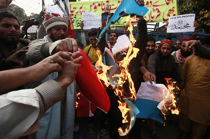 Supporters of religious groups burn a replica of French flag during a protest against satirical French weekly newspaper Charlie Hebdo, in Lahore January 23, 2015. (Reuters/Mohsin Raza)