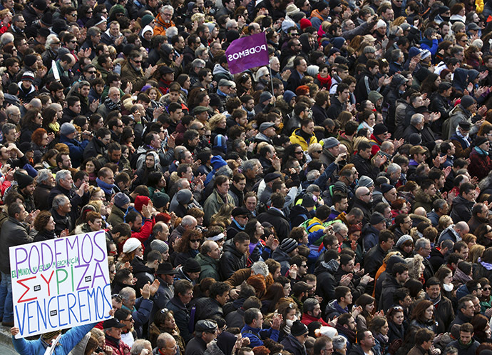A man holds up a banner as people gather during a rally called by Spain's anti-austerity party Podemos, at Madrid's Puerta del Sol landmark January 31, 2015. (Reuters/Sergio Perez)