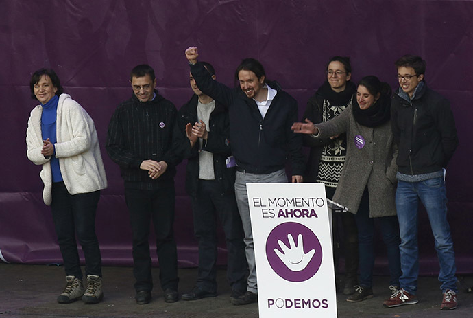 """Pablo Iglesias (C), leader of Spain's party """"Podemos"""" (We Can), raises his fist as he stands with his party members on the stage during a rally called by Podemos, at Madrid's Puerta del Sol landmark January 31, 2015. (Reuters/Sergio Perez)"""