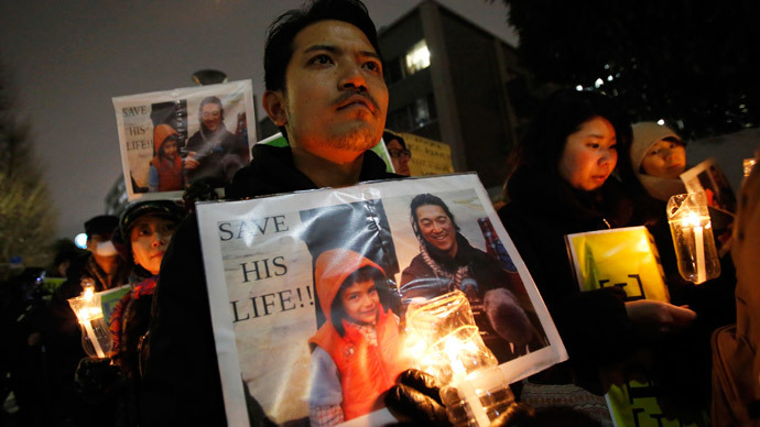 People holding placards take part in a vigil in front of Prime Minister Shinzo Abe's official residence in Tokyo, January 30, 2015.(Reuters / Toru Hanai)