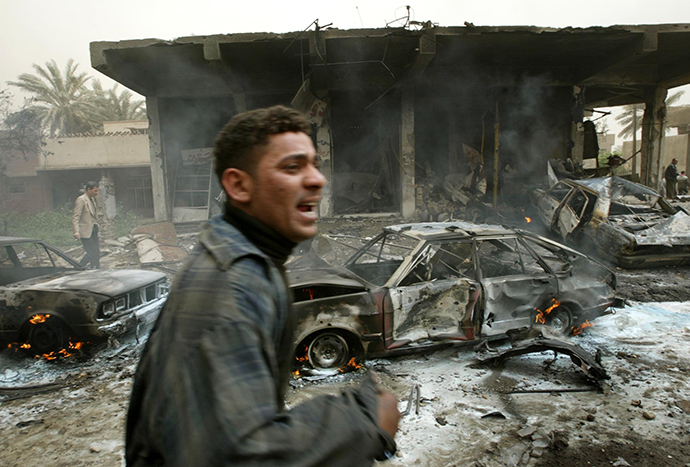 An Iraqi man cries as he runs past a burning car destroyed during an air strike in Baghdad, March 26, 2003 (Reuters)
