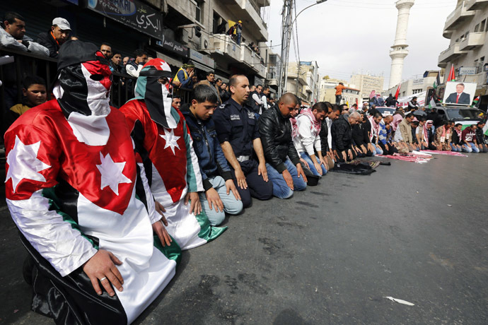 Protesters dressed in Jordanian flag perform Friday prayers along a street outside al-Husainy mosque before a march in downtown Amman February 6, 2015. (Reuters/Muhammad Hamed)