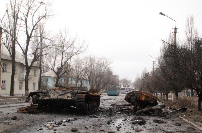 Burnt military machinery in Uglegorsk. Background: a bus column from DPR heading to Debaltsevo for evacuation of local residents from the combat zone. (RIA Novosti)