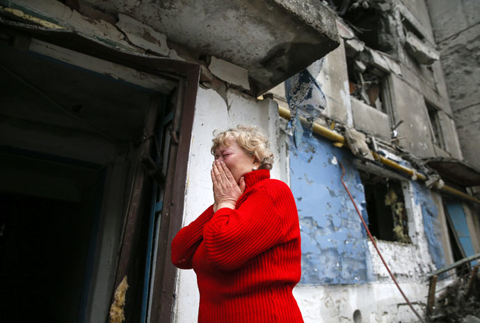 A woman reacts as she stands near a multi-storey block of flats damaged by shelling in Yenakieve town, northeast from Donetsk, February 2, 2015. (Reuters/Maxim Shemetov)