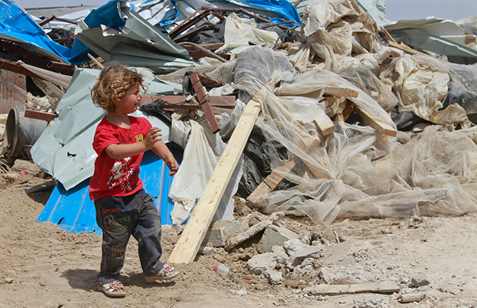 A Palestinian girl walks past her family's house after it was demolished by Israeli bulldozers in Om Ajaj village, north of the West Bank city of Jericho (Reuters / Abed Omar Qusini)