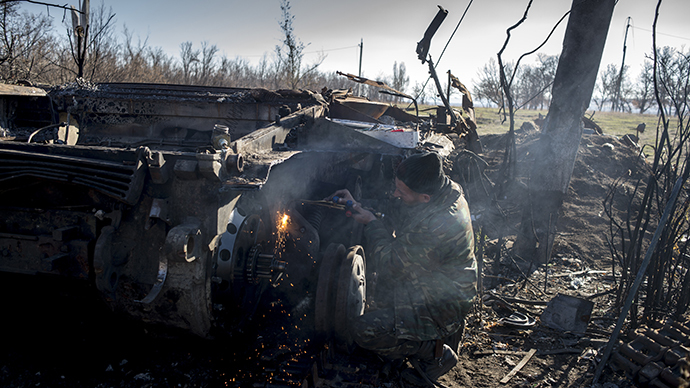 A militiaman of the People's Republic of Lugansk inspects a burnt-out Ukrainian tank in Novosvetlovka. (RIA Novosti / Valeriy Melnikov)