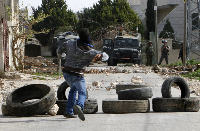A Palestinian protester throws stones at Israeli border policemen during clashes following a protest against the near-by Jewish settlement of Qadomem, in the West Bank village of Kofr Qadom near Nablus February 6, 2015. (Reuters)