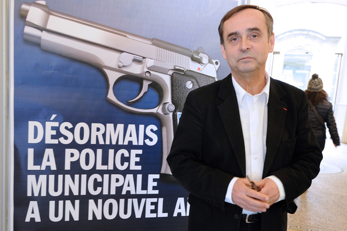 "Beziers mayor Robert Menard poses on February 11, 2015 in front of a municipality campaign poster showing an automatic 7.65 handgun, with a campaign slogans reading : ""From now on, the Municipal Police has a new friend"". (AFP Photo / Sylvain Thomas)"