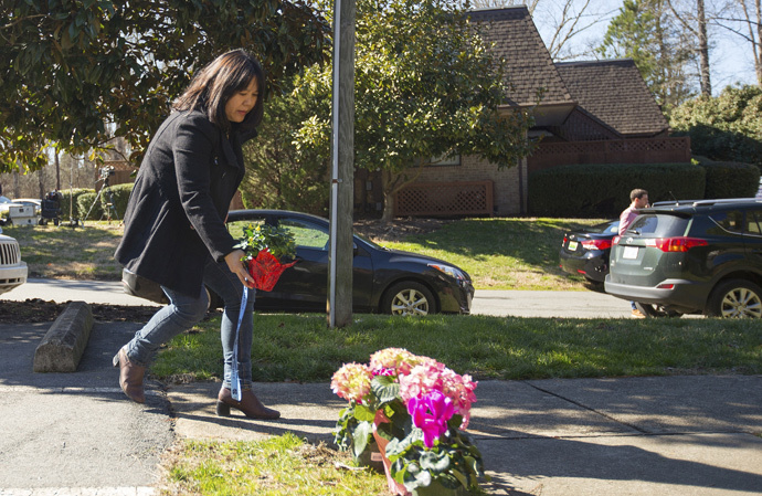 A woman places flowers near a building where three young Muslims were killed on Tuesday, in Chapel Hill, North Carolina February 11, 2015. (Reuters / Chris Keane)