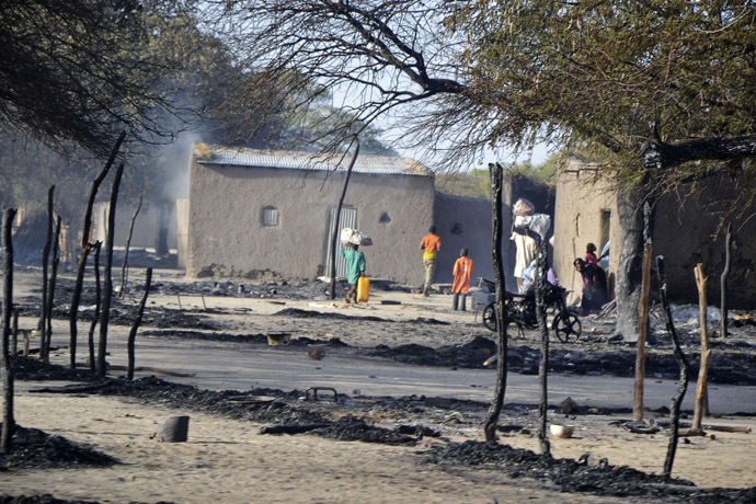 People walk in a burnt compound after an attack by Boko Haram militants in the village of Ngouboua February 13, 2015. (Reuters/Madjiasra Nako)