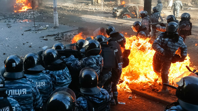 Riot policemen stand guard as they are hit by fire caused by molotov cocktails hurled by anti-government protesters during clashes in Kiev February 18, 2014.(Reuters / Stringer)