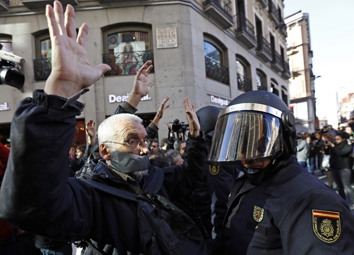 A man, with his mouth taped, faces off with a Spanish riot policeman during a protest against the Spanish government's new anti-protest security law in Madrid December 20, 2014. (Reuters / Sergio Perez)