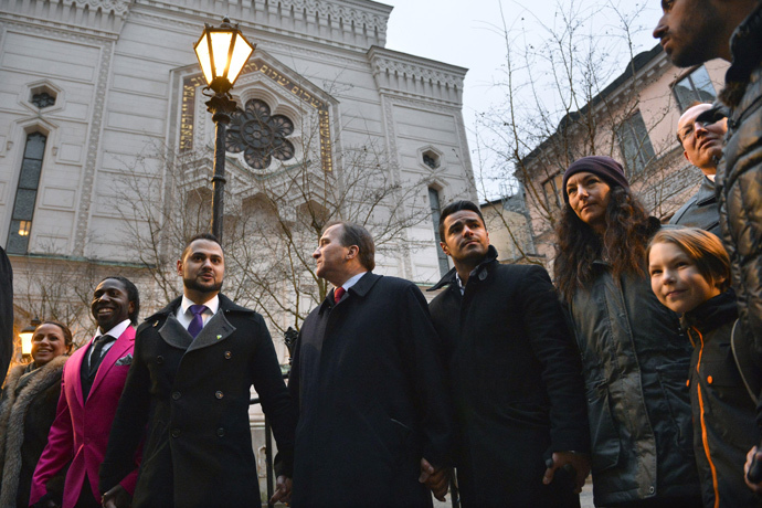 "Swedish Prime Minister Stefan Lofven (C) holds hands with the representatives of various minority group organisations Emir Selimi (C, left) Mohammed Mouaid (C, right) and Petra Kahn Nord with her son Gabriel (R), as people gather to form a ""ring of peace"" around The Great Synagogue of Stockholm at Raoul Wallenberg, in central Stockholm February 27, 2015. (Reuters / Henrik Montgomery / TT News Agency)"