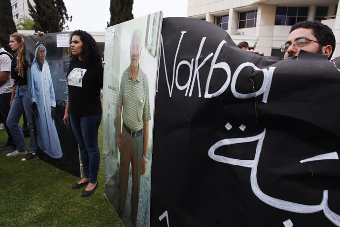 Pro-Palestinian demonstrators hold boards during a rally marking Nakba Day, outside Tel Aviv University (Reuters/Nir Elias)