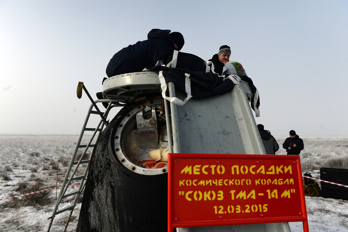 Russia's space agency ground personnel check the Soyuz capsule shortly after it landed in a remote area outside the town of Zhezkazgan in central Kazakhstan, March 12, 2015. (Reuters / Vasily Maximov / Pool)