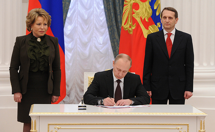 Russian President Vladimir Putin (C) signs documents as Sergey Naryshkin (R), speaker of the State Duma, Russia's lower parliament house, and Valentina Matviyenko, head of the Federation Council, look on during a ceremony in Moscow's Kremlin March 21, 2014 (RIA Novosti / Mikhail Klimentyev)