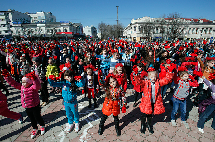 "Children take part in the flash mob segment of the ""This is dedicated to you, Russia!"" theatrical performance to celebrate the first anniversary of Russia's annexation of Ukraine's Black Sea peninsula of Crimea, in central Simferopol March 14, 2015 (Reuters / Maxim Shemetov)"