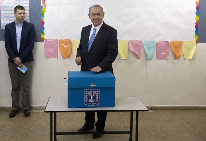 Israel's Prime Minister Benjamin Netanyahu casts his ballot for the parliamentary election as his son Yair stands behind him at a polling station in Jerusalem March 17, 2015. (Reuters/Sebastian Scheiner)