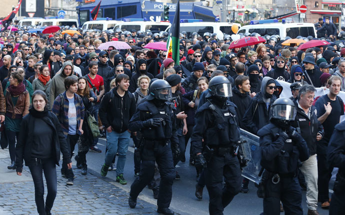 German riot police officers walk along marching protesters in Frankfurt, March 18, 2015. (Reuters/Michael Dalder)