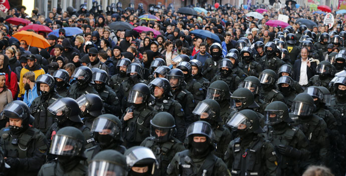 German riot police officers walk along marching protesters in Frankfurt, March 18, 2015. (Reuters/Wolfgang Rattay)