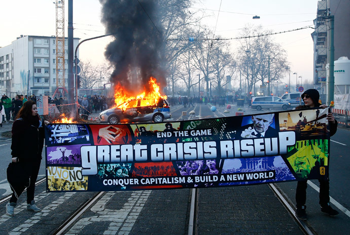 Anti-capitalist protesters pose in front of a burning German police car that was set on fire in the early morning hours near the European Central Bank (ECB) building before the official opening of its new headquarters in Frankfurt March 18, 2015. (Reuters / Kai Pfaffenbach)