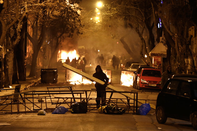 A masked youth places a wooden beam at a barricade during clashes with riot police in Athens March 17, 2015. (Reuters / Alkis Konstantinidis)