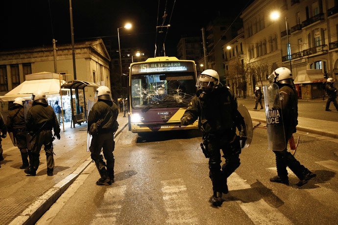 Riot police stand in front of a destroyed trolley bus during clashes with masked youth in Athens March 17, 2015. (Reuters / Alkis Konstantinidis)