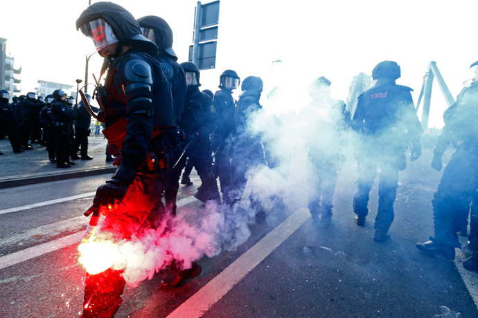 A policeman holds a flare during a protest of members of 'Blockupy' anti-capitalist movement near the European Central Bank (ECB) building before the official opening of its new headquarters in Frankfurt March 18, 2015. (Reuters / Ralph Orlowski)