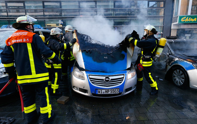 Fireworkers extinguish police vehicles set of fire by anti-capitalist 'Blockupy' protesters near the European Central Bank (ECB) building before the official opening of its new headquarters in Frankfurt March 18, 2015. (Reuters / Ralph Orlowski)