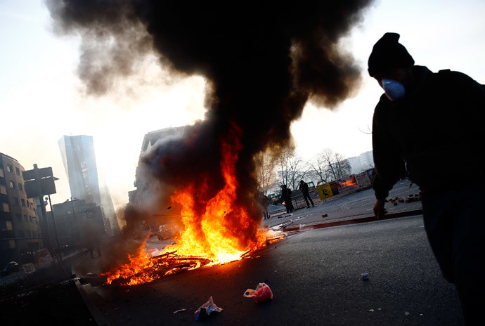 A 'Blockupy' anti-capitalist protester walks near a burning barricade near the European Central Bank (ECB) building before the official opening of its new headquarters in Frankfurt March 18, 2015. (Reuters / Kai Pfaffenbach)