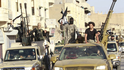 Militant Islamist fighters in military vehicles parade along the streets of Syria's northern Raqqa province June 30, 2014. (Reuters)