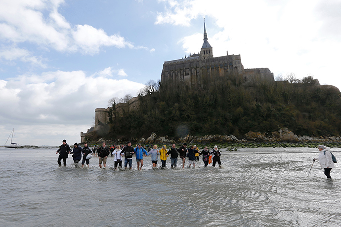 Tourists walk through retreating waters with a bay guide around the Mont Saint-Michel 11th century abbey off France's Normandy coast March 21, 2015 (Reuters / Pascal Rossignol)
