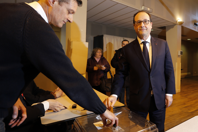 French President Francois Hollande (R) casts his ballot in the first round of French local elections, as he votes in Tulle, central France, March 22, 2015. (Reuters / Regis Duvignau)