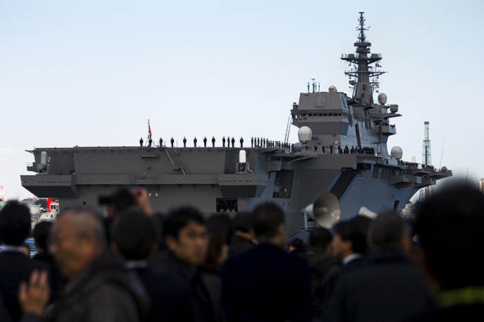 People watch the departure of the Izumo warship from the harbour of Japan United Marine shipyard in Yokohama, south of Tokyo March 25, 2015 (Reuters / Thomas Peter)