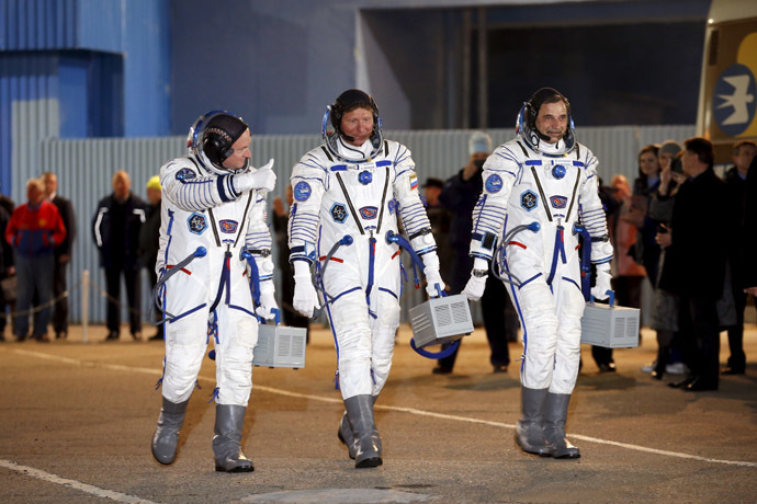 International Space Station (ISS) crew of (L-R) Scott Kelly of the U.S. and Mikhail Kornienko and Gennady Padalka of Russia walk after donning space suits at the Baikonur cosmodrome March 27, 2015 (Reuters/Maxim Zmeyev)