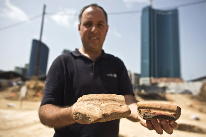 Diego Barkan, director of the excavation for the Israel Antiquities Authority (IAA), shows fragments of ancient basins unearthed at an archaeological dig in a future construction site in Tel Aviv March 29, 2015. (Reuters / Nir Elias)